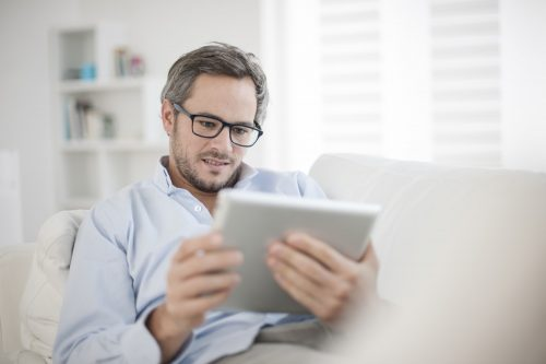 Attractive Man At Home Using Digital Table